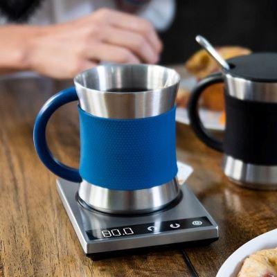 a stainless steel mug sitting on a flat mug warmer hot plate