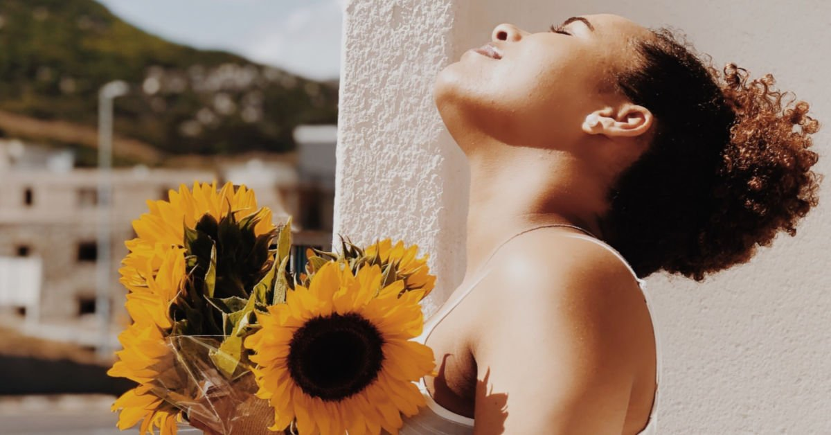 happy woman holding yellow sunflower bouquet gift