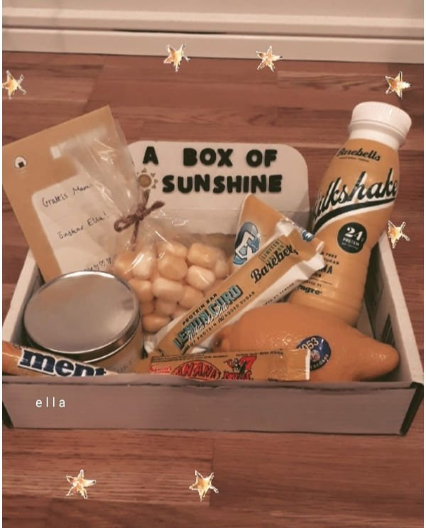 "small cardboard box labeled ""a box of sunshine"". In it are yellow candies, a milkshake, a candle and a lemon"