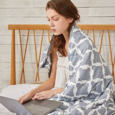 a college girl working on her laptop in bed with a pattern weighted blanket wrapped around her