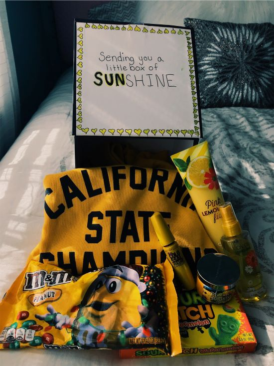 yellow california state sweatshirt and snacks on a bed