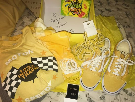 yellow shirt, vans, stickers, scarf and candy on a bed