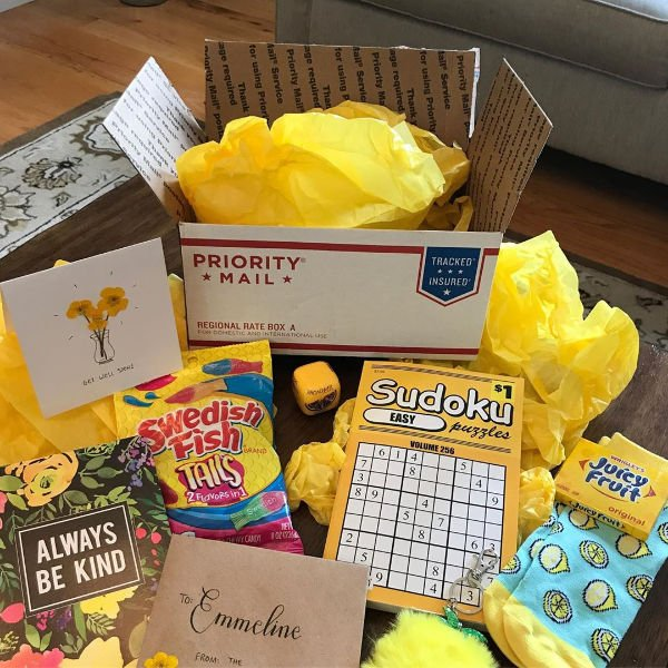 opened care package with sudoku, juicy fruit gum, candy, socks and a card on a coffee table