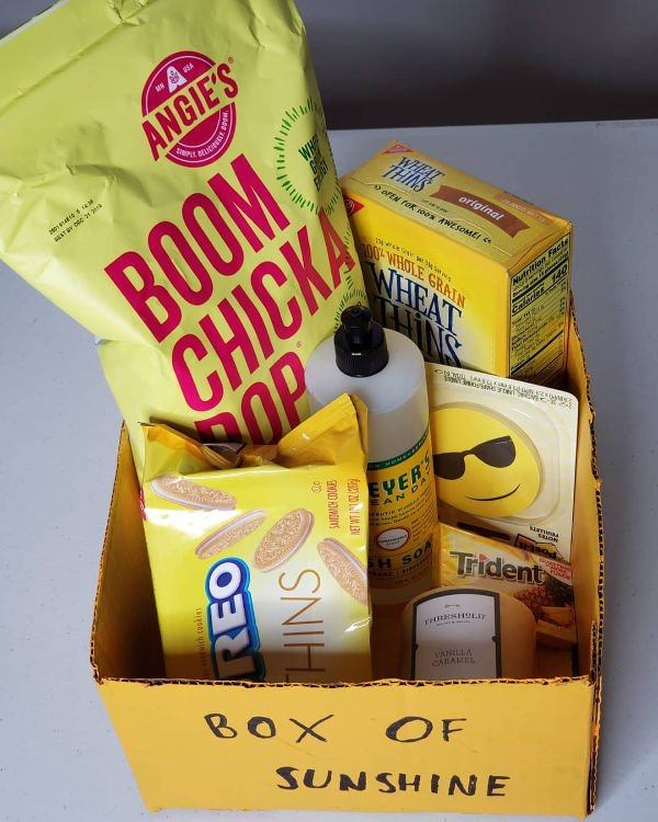 yellow cardboard box with blonde oreos, boom chicka pop, wheat thins & more for sunshine gift
