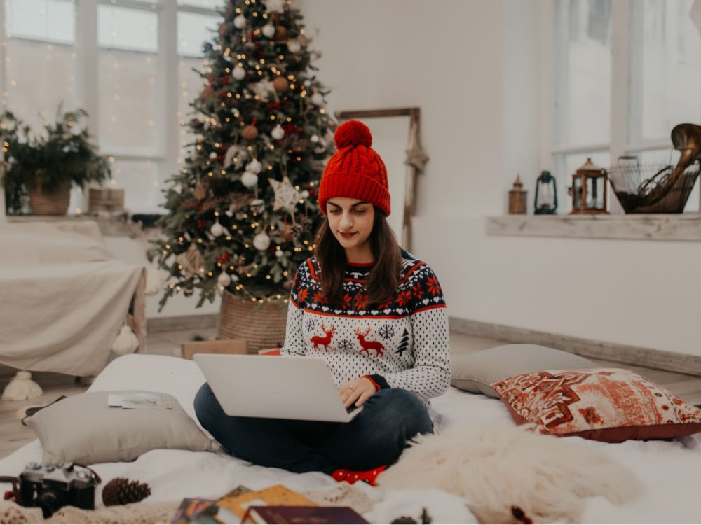 college student in red beanie and holiday sweater looking at December deadline scholarships on laptop