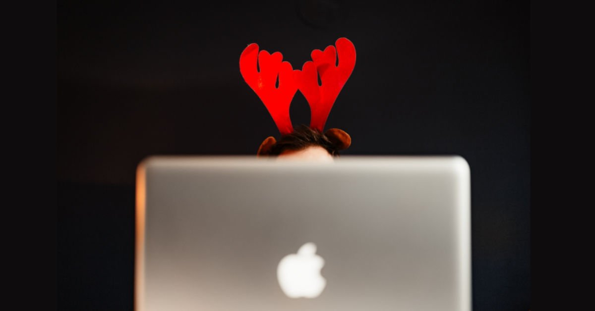 red reindeer antlers poking over the top of a mac book