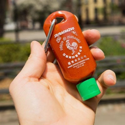 hand holding a Sriracha Mini Keychain