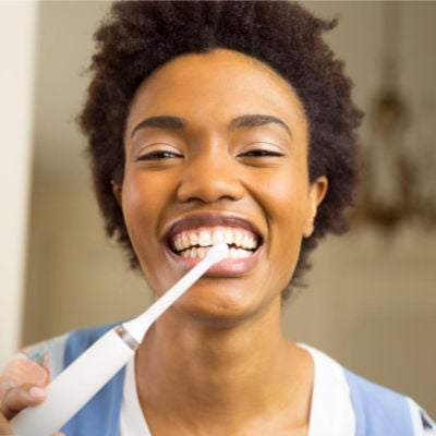 girl brushing her teeth with a big smile