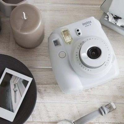 white Polaroid picture camera next to a picture