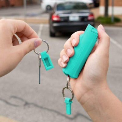 college girl holding blue keychain pepper spray