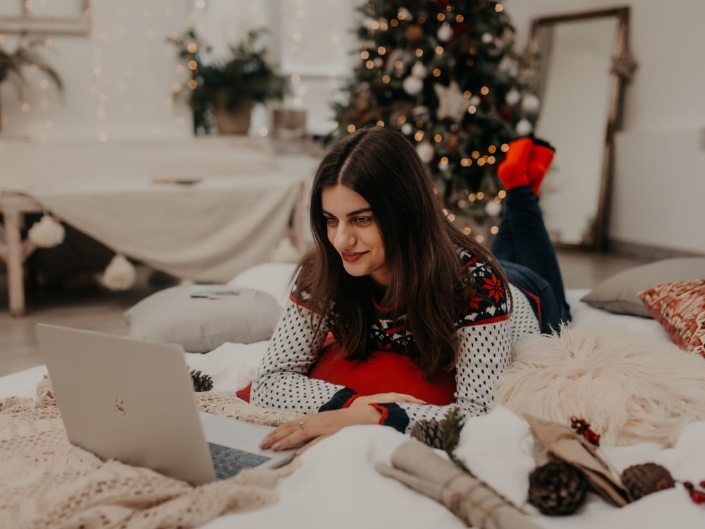 college girl applying for winter scholarships on her laptop during the holidays