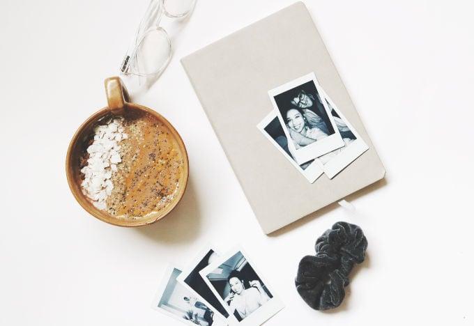 bullet journal beside polaroids and brown mug