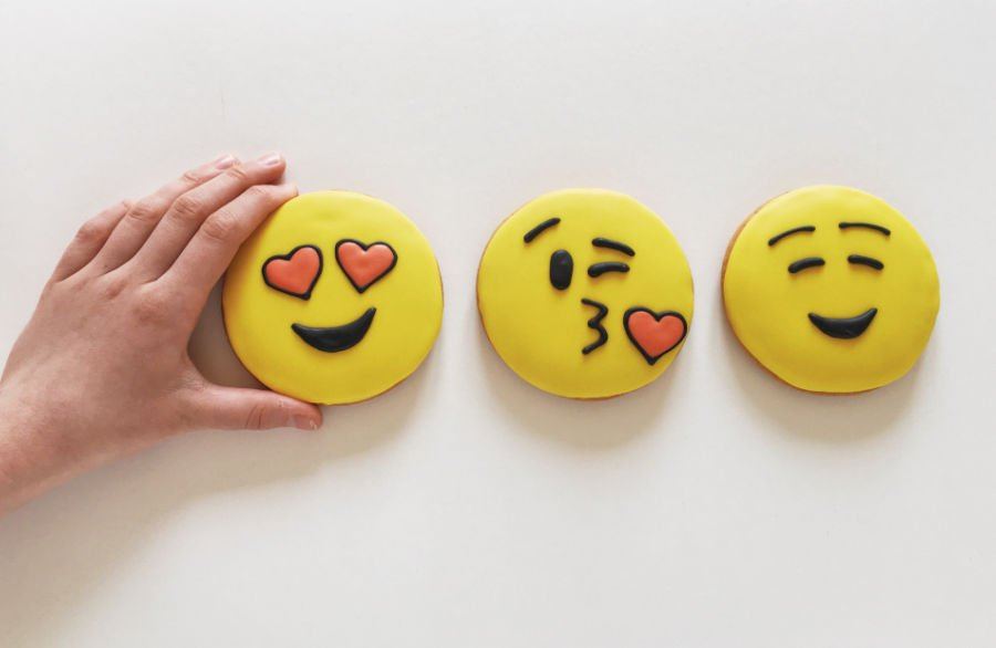three cookies in a row made to look like heart eyes emoji, blowing a kiss emoji, and happy emoji
