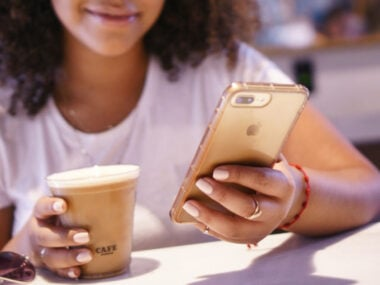 smiling young black woman using phone while having coffee at a cafe