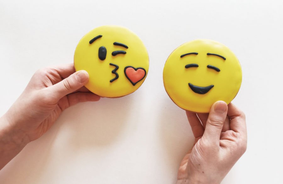 hands holding kissing emoji and smiling emoji cookies