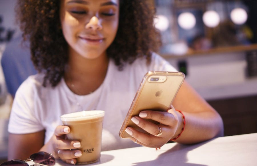 black millennial smiling while looking at scholarships on her gold iphone