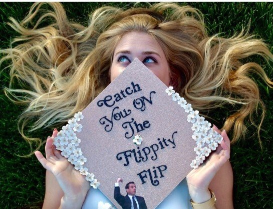 graduate holding the office graduation cap in front of her face