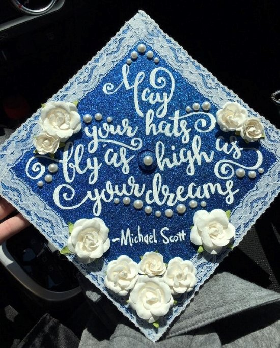 blue grad cap decorated with glitter, flowers, and a quote from The Office tv show