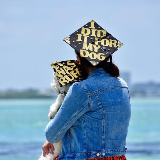 graduating student and her dog wearing dog mom grad caps