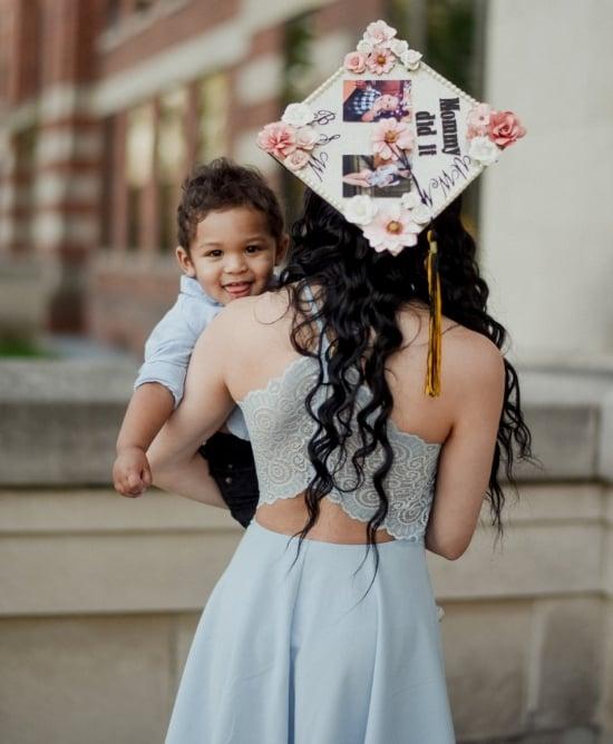 college graduate mom holding son for grad cap picture