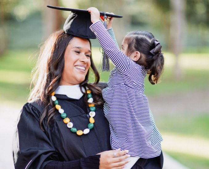 smiling mother and child grabbing graduation cap