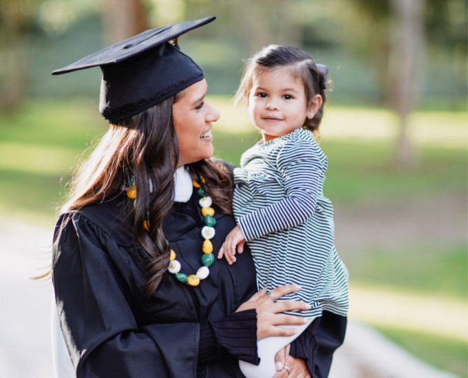 college graduate mother in cap and gown holding young daughter