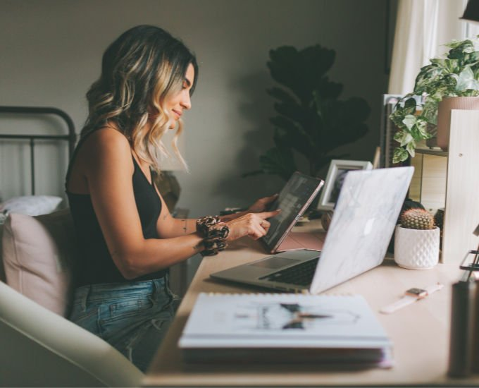 happy millennial woman applying for scholarships on tablet