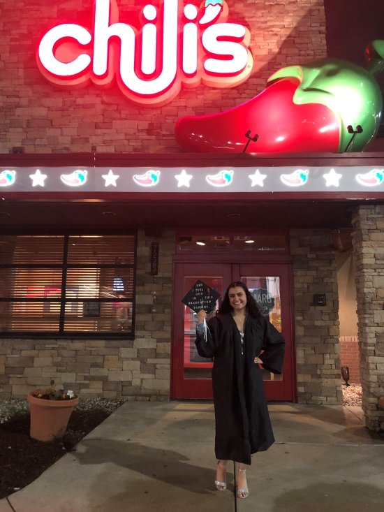 smiling graduate holding the office graduation cap in front of Chili's