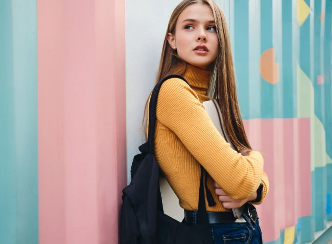 college student looking pensive with laptop and backpack for school