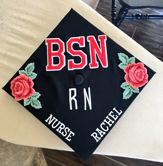"""grad cap decorated with the words """"BSN RN Nurse Rachel"""" and red roses on the corners"""