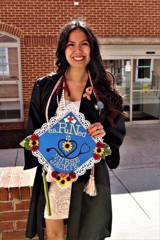 smiling nurse college graduate posing with decorated graduation hat