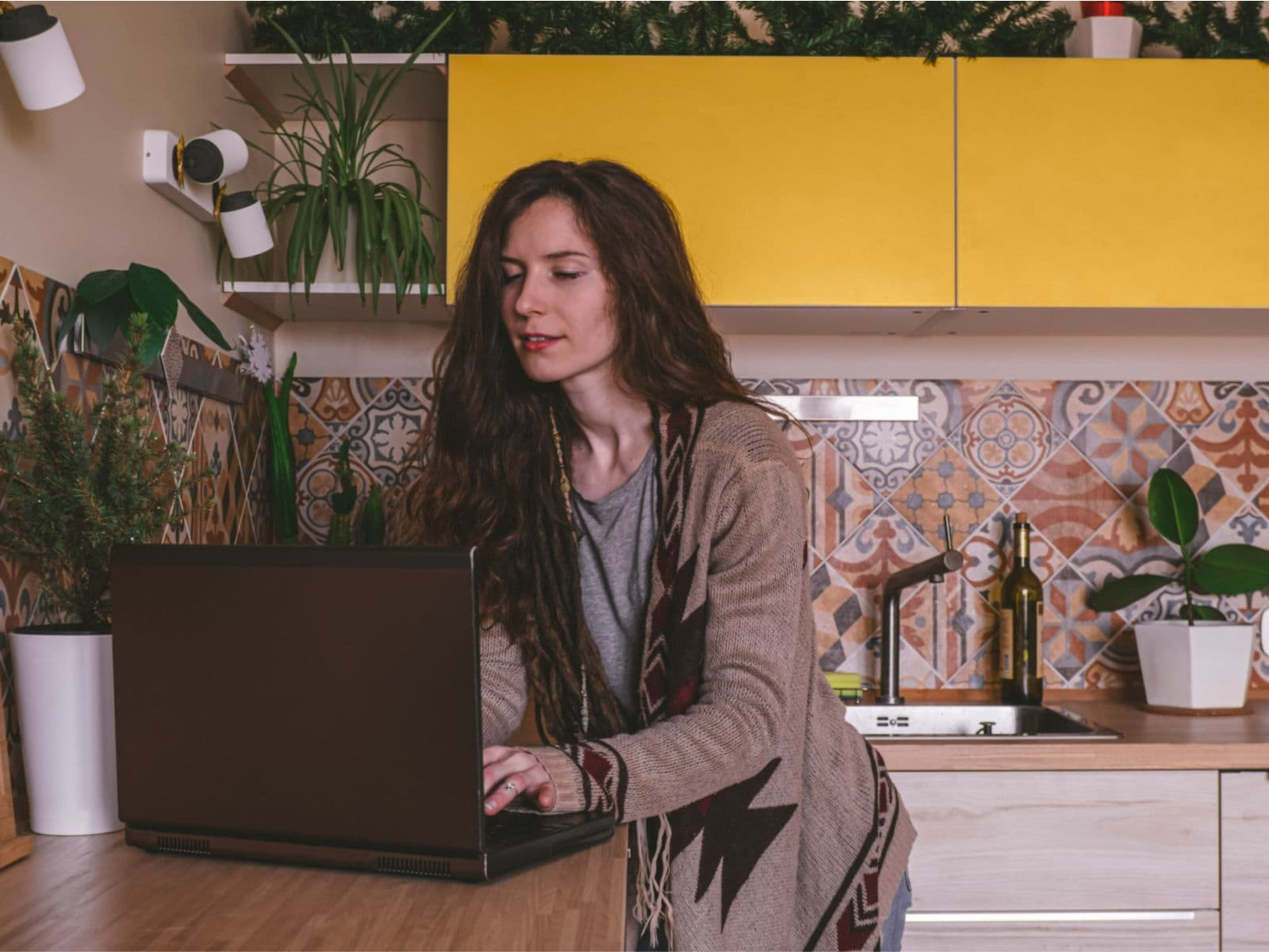 college woman looking thoughtful while using the internet on her laptop in the kitchen