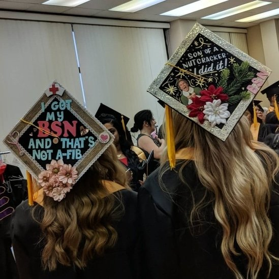 two new grad nurses showing off graduation caps
