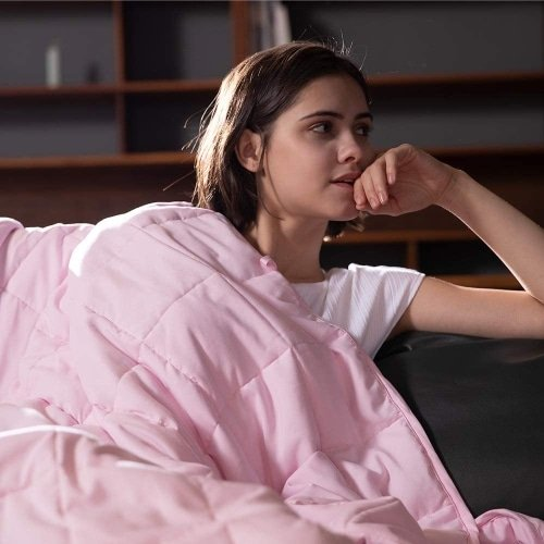 young woman looking to the right while draped with a pink weighted blanket