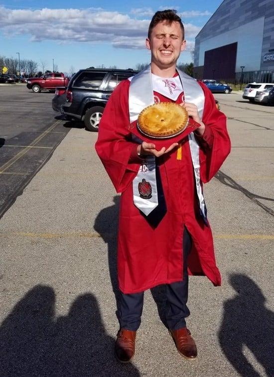 happy graduate with pie decorating graduation cap