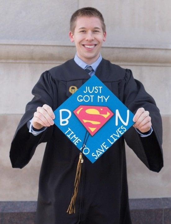 "smiling guy graduate with ""just got my BSN"" superman grad cap"