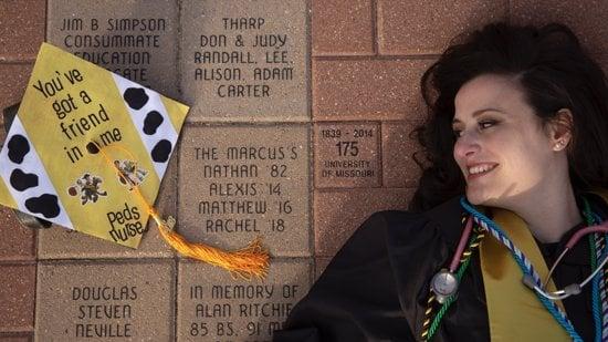 college graduate smiling at her pediatric nurse decorated yellow cap