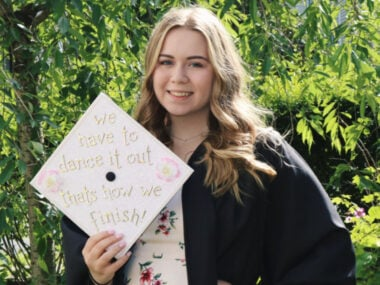 RN graduate posing with her grey's anatomy quote graduation cap