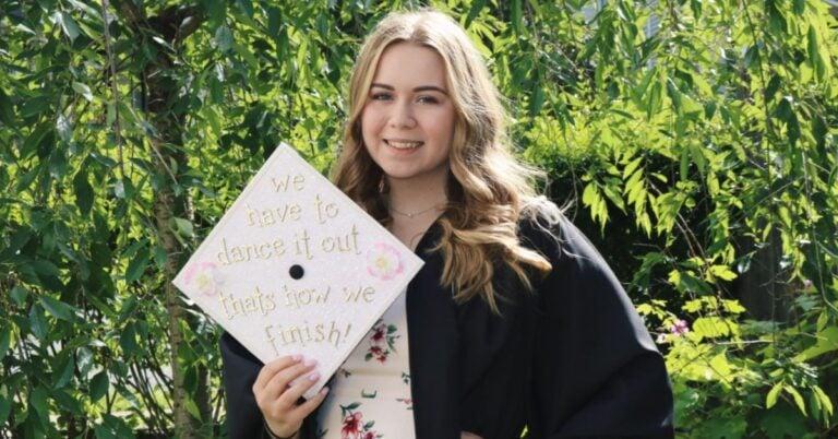 RN graduate posing with her grey's anatomy quote graduation cap