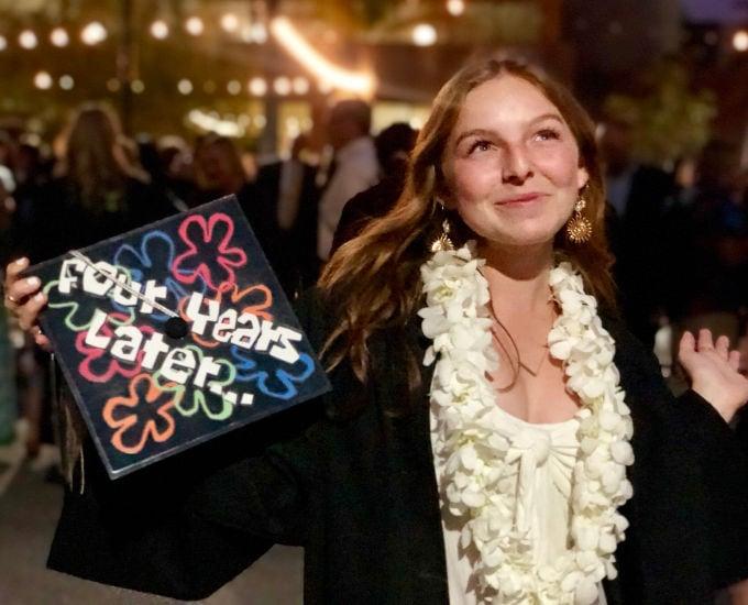 happy college grad holding her spongebob themed graduation cap