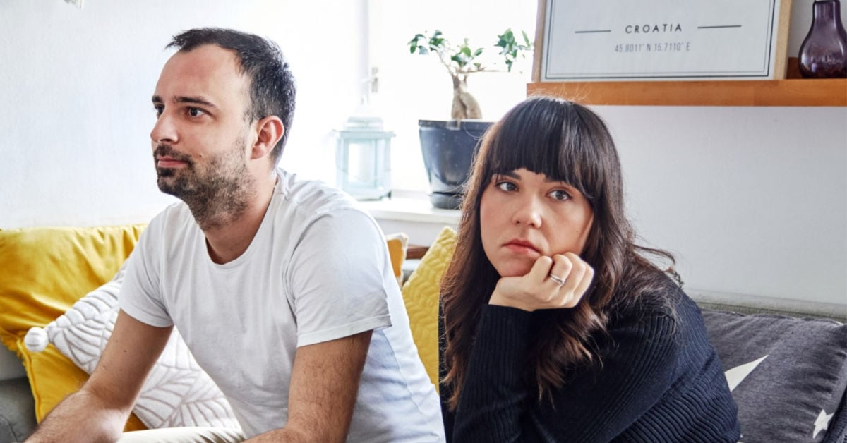 woman and man at home with bored expressions on their faces
