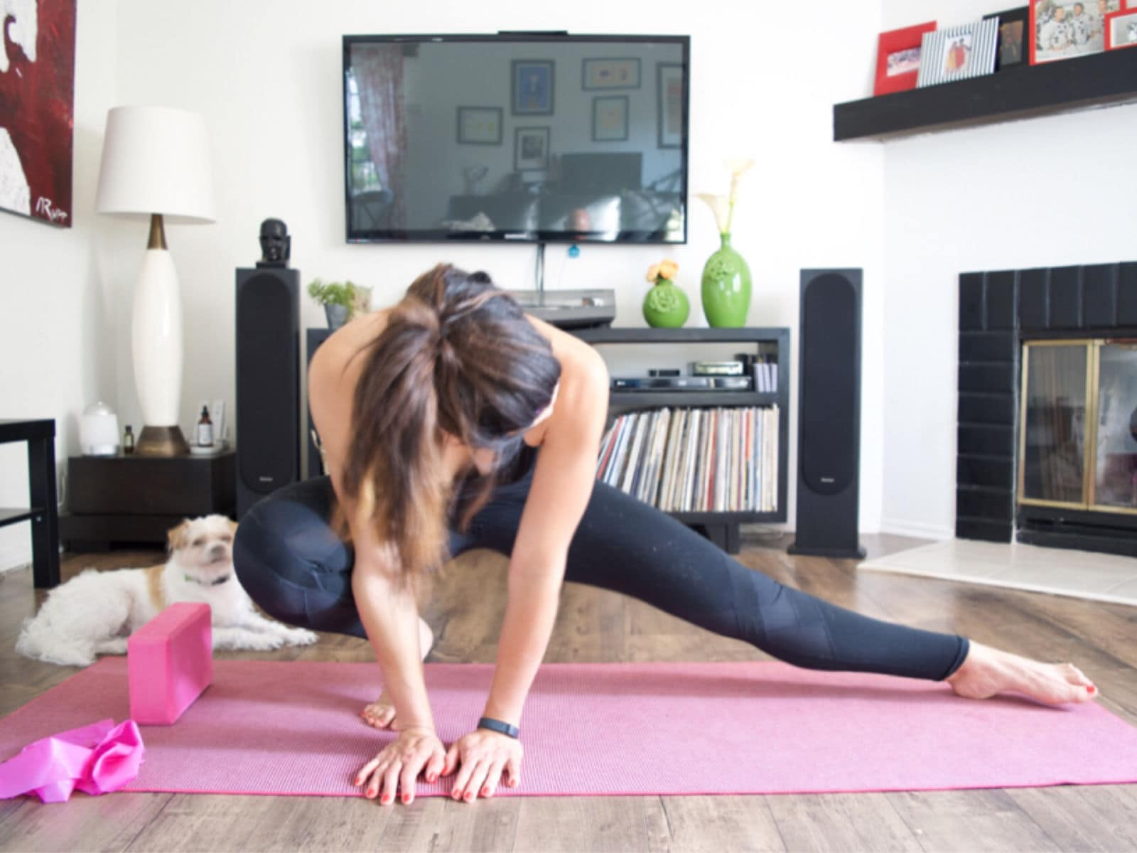 woman doing a home workout with her small dog in the background