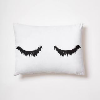 white throw pillow with eyelash design