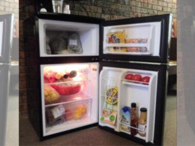 opened mini fridge with freezer showing its stocked with food