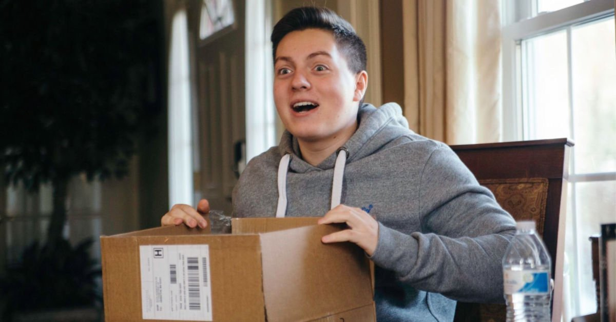 excited college guy opening a care package
