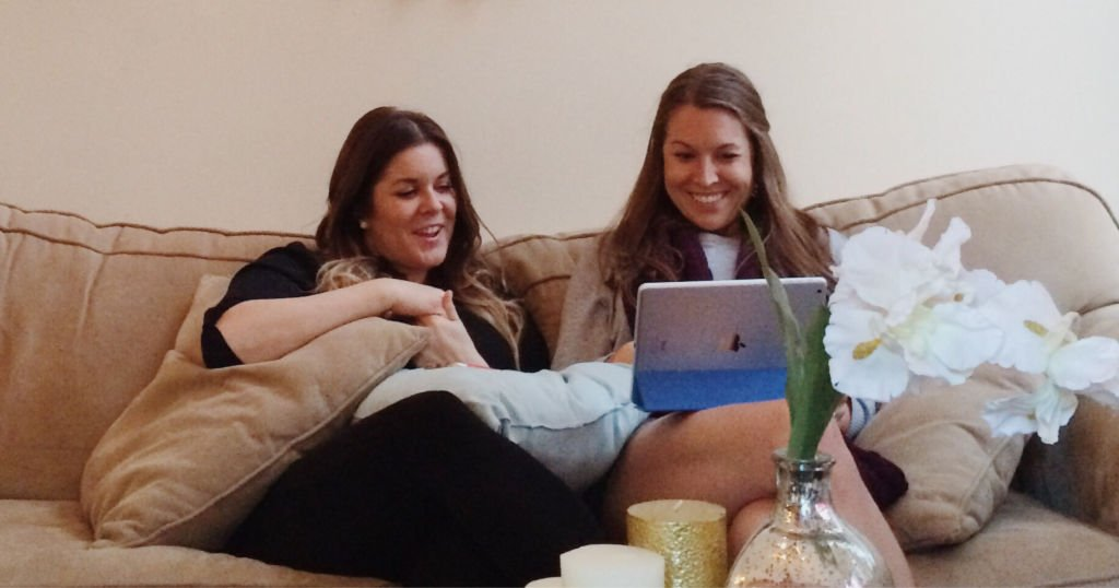 two women sitting on a couch excitedly looking at college scholarships on a laptop