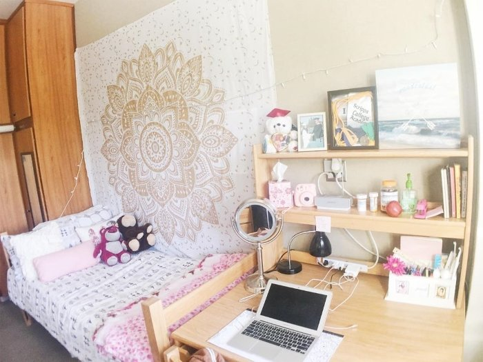 dorm room at UCLA with gold tapestry on wall and pink decor