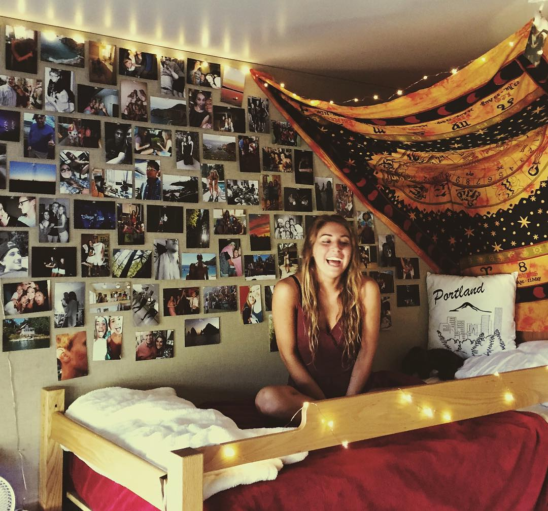 happy female UCLA student sitting on her dorm bed. room decorated with photos on wall, tapestry and string lights