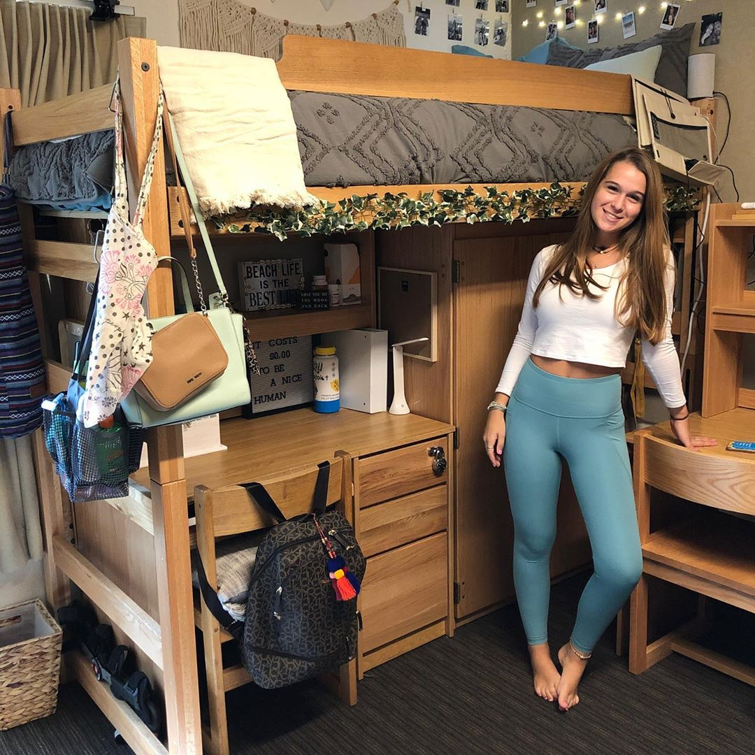 college girl standing next to her bed at the UCLA dorms