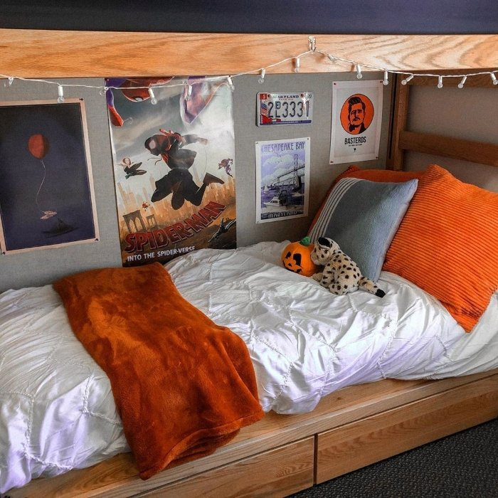 UCLA dorm with white bedspread and orange decor accents